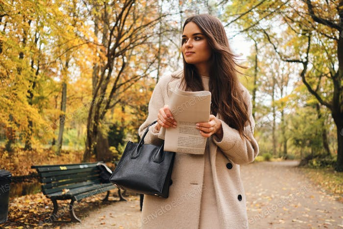 Beautiful brunette girl with newspaper dreamily walking alone in autumn park