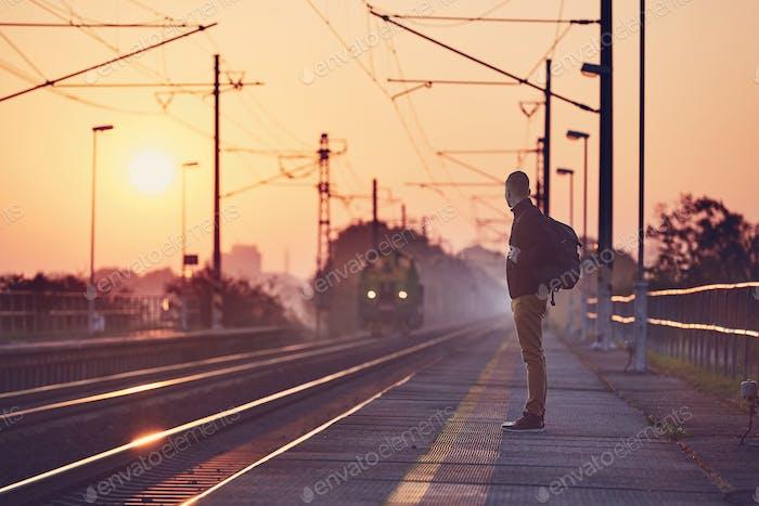 Alone man waiting at railroad station