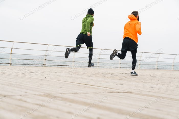 Two motivated young sportsmen jogging outdoors