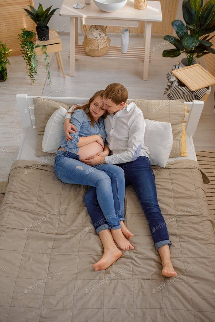 Portrait of future parents on the bed shot from the top angle