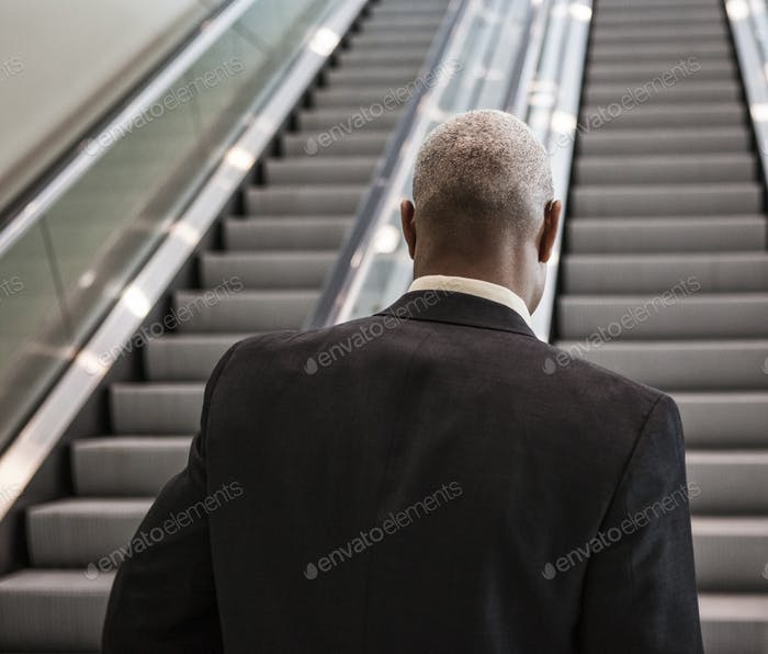 Black businessman on his way up an office escalator.