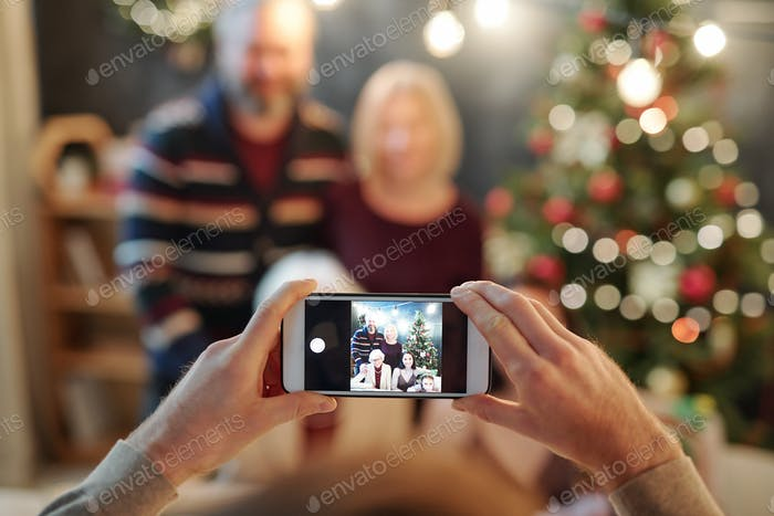 Hands of man holding smartphone while taking photo of big relaxed family