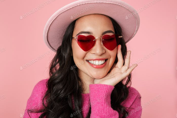 Image of asian girl with long dark hair wearing hat and sunglasses smiling