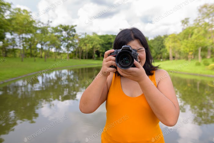Beautiful overweight Asian woman photographer taking picture in park