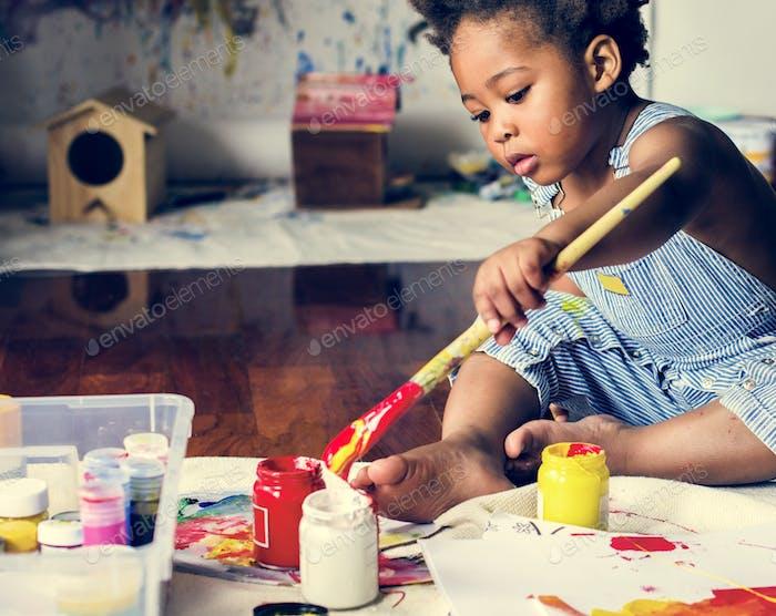Black kid enjoying color painting