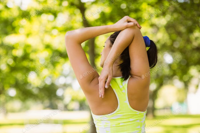 Rear view of a fit brunette stretching in the park