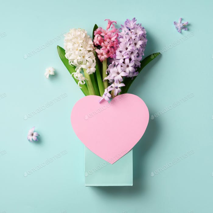 Spring hyacinth flowers in shopping bag, pink paper heart on blue punchy pastel background. Square