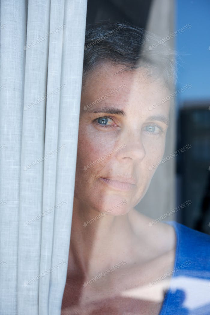 Close up middle age woman looking through window