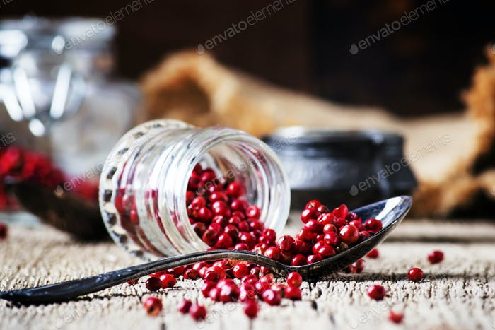 Pink pepper in spoon and jar