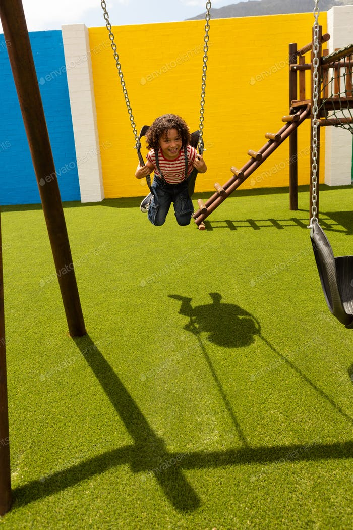 Front view of mixed-race schoolgirl playing on a swing at school playground on a sunny day