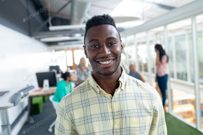 Portrait of happy African-american businessman looking at camera in a modern office