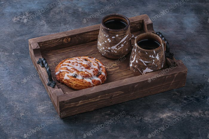 Sweet pastry with cup of coffee on wooden board