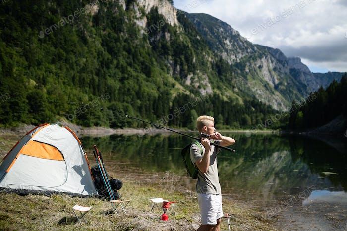Fisherman fishing in nature at lake while camping outdoor