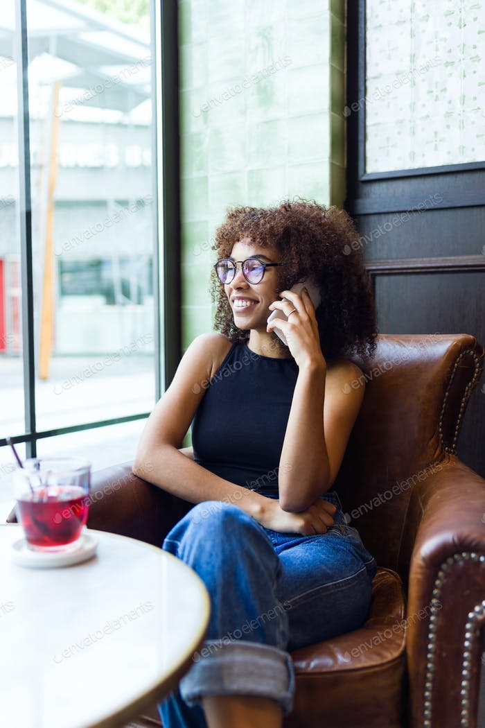 Beautiful young woman using her mobile phone in cafe.