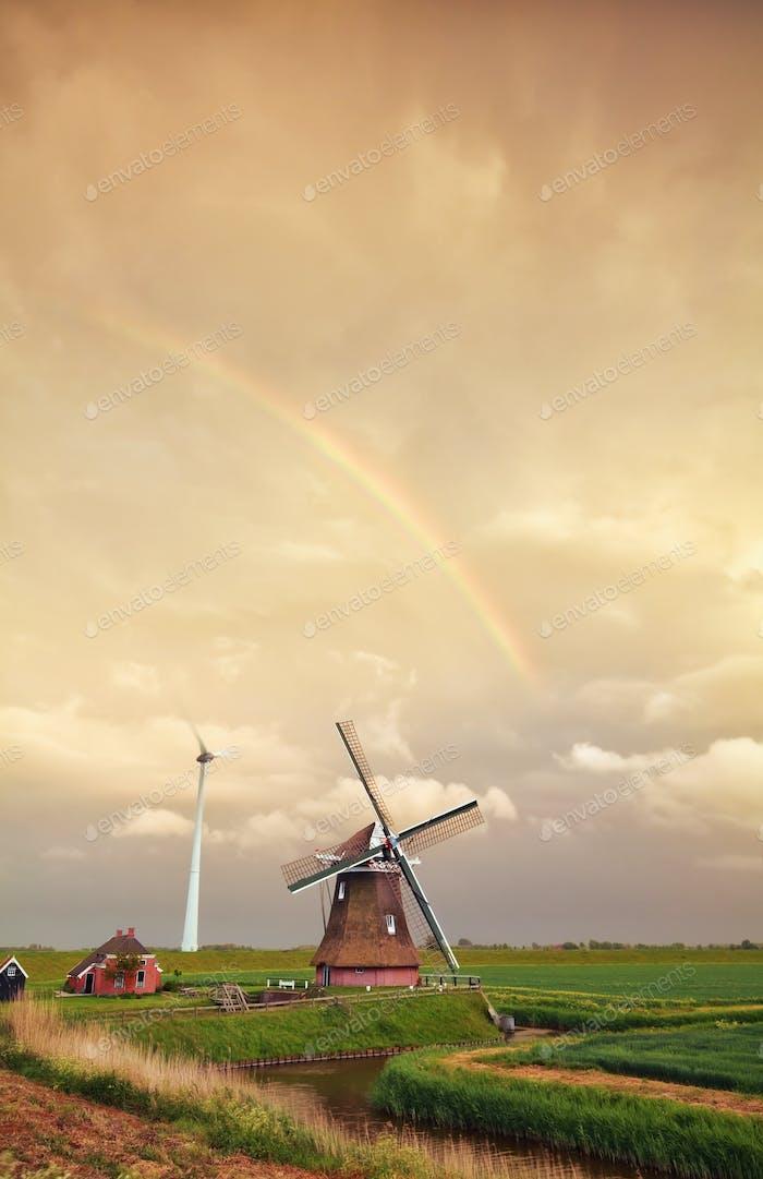 rainbow over Dutch windmill at sunset