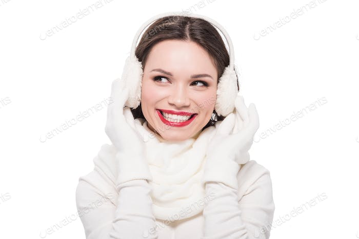 Portrait of young smiling woman in scarf, gloves and earmuffs , isolated on white