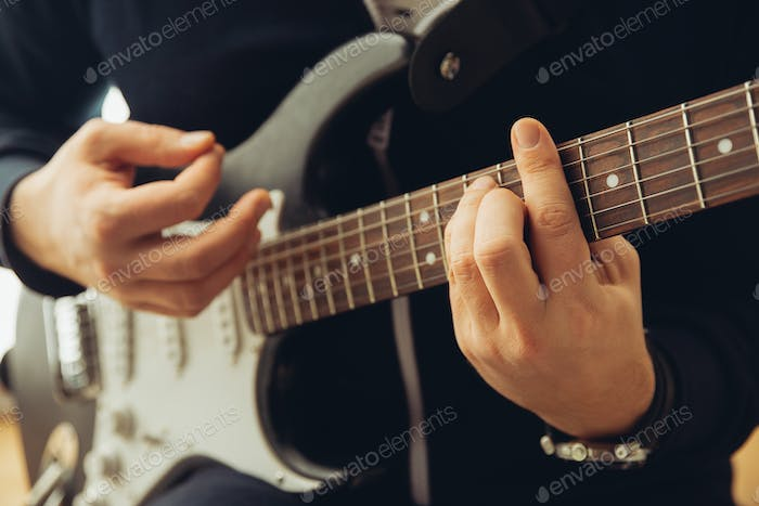 Caucasian musician playing guitar during concert at home isolated and quarantined, cheerful