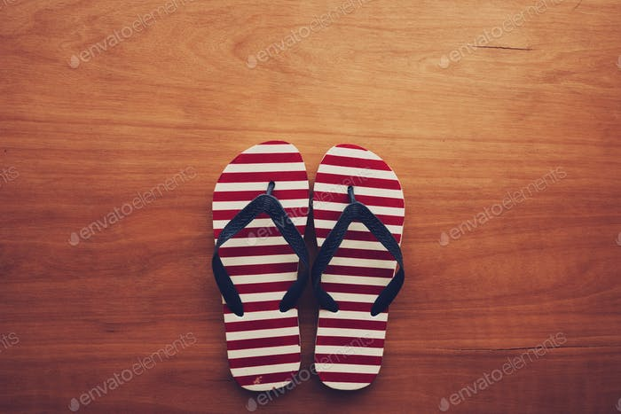 Beach sandals flip flops on wooden background