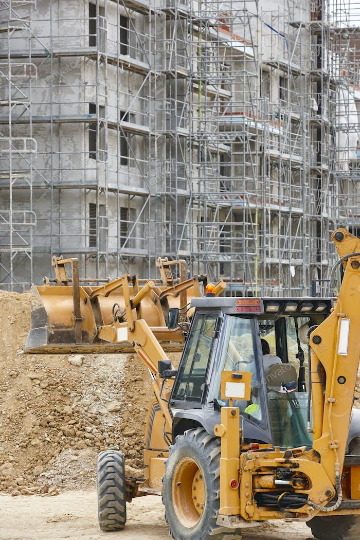 Bagger auf einer Baustelle. Bauen im Gange. Architektur. Vertikal
