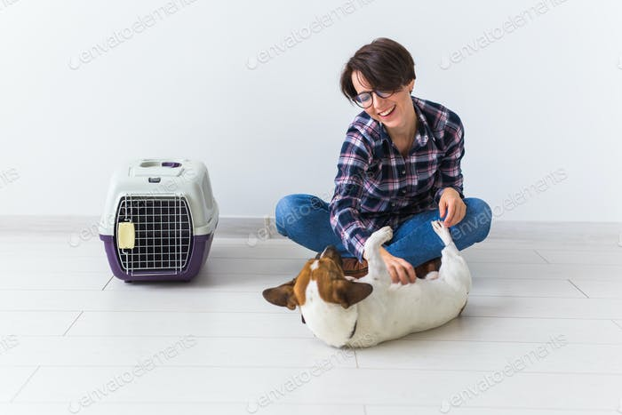 Pets owner concept - Attractive cheerful female in plaid shirt holds favourite pet. Happy woman with