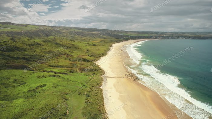 Aerial coast beach: Atlantic Ocean, Antrim county, Northern Ireland. People walking on sandy shore