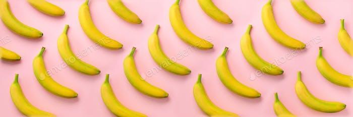 Geometrisches buntes Fruchtmuster. Bananen über rosa Hintergrund. Banner. Draufsicht. Pop Art-Design