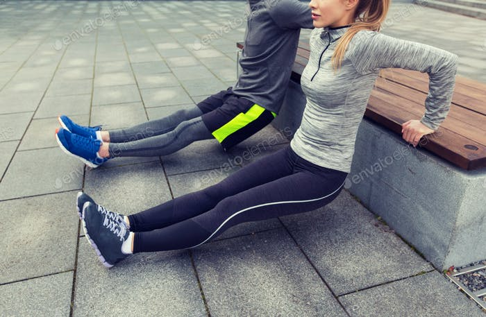 close up of couple doing triceps dip on bench