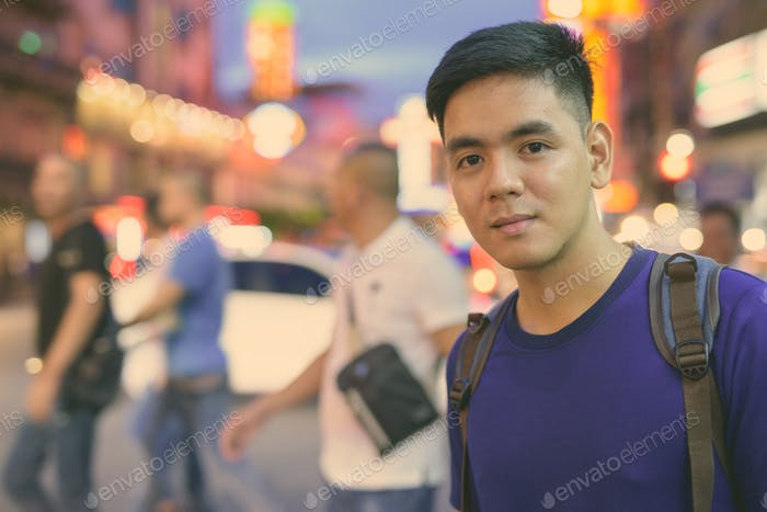 Young handsome Asian tourist man exploring at Chinatown in Bangkok, Thailand