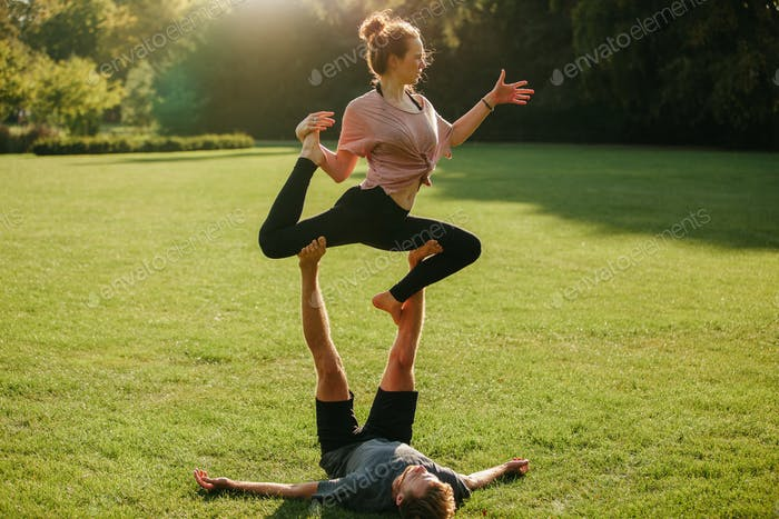Man and woman doing various yoga poses in pair