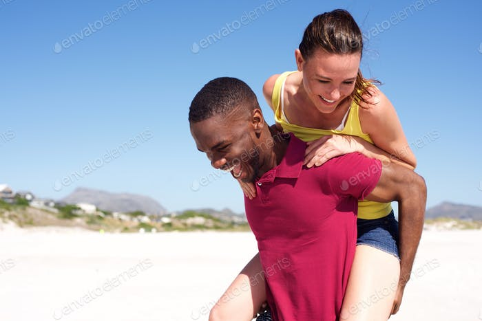 Man carrying woman on back at the beach
