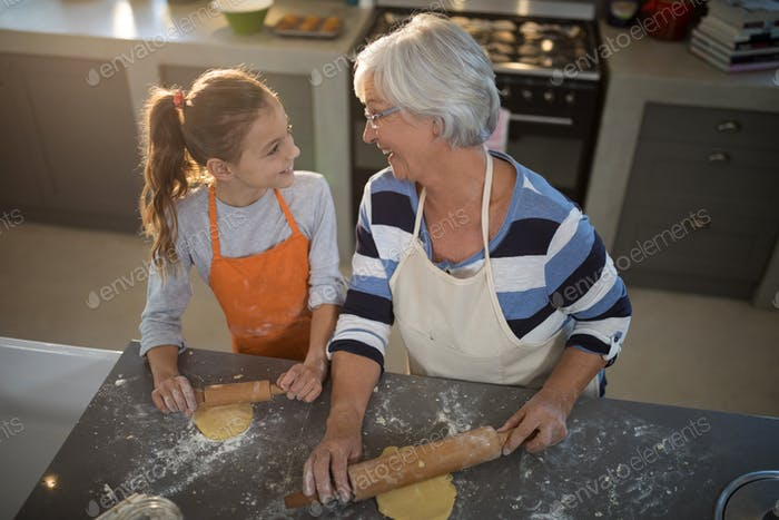Grandmother and granddaughter looking at each other while flattening dough