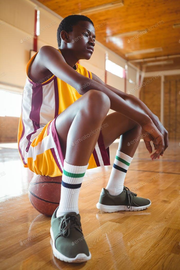 Thoughtful teenage boy sitting on basketball