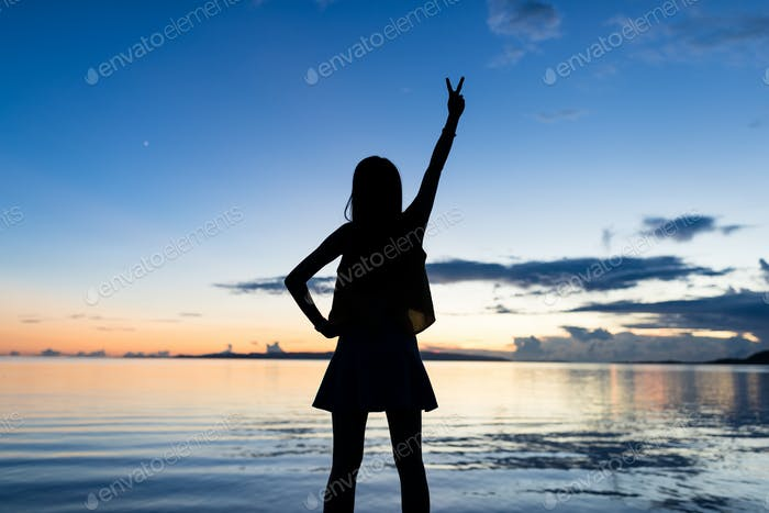 Silhouette of woman raising hand up