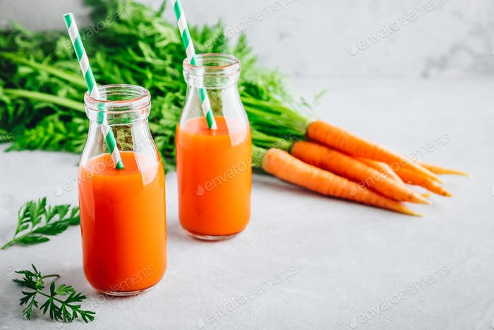 Fresh detox carrot juice in glass bottles on a gray stone background
