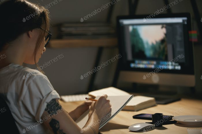 Young lady designer sitting indoors at night drawing sketches