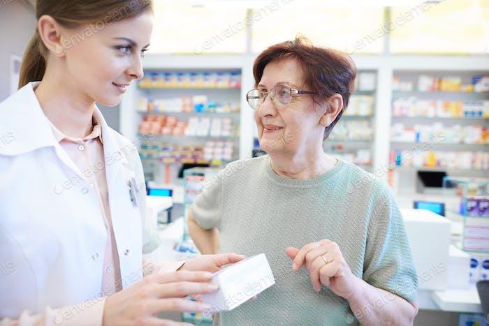 Female pharmacist assisting senior woman