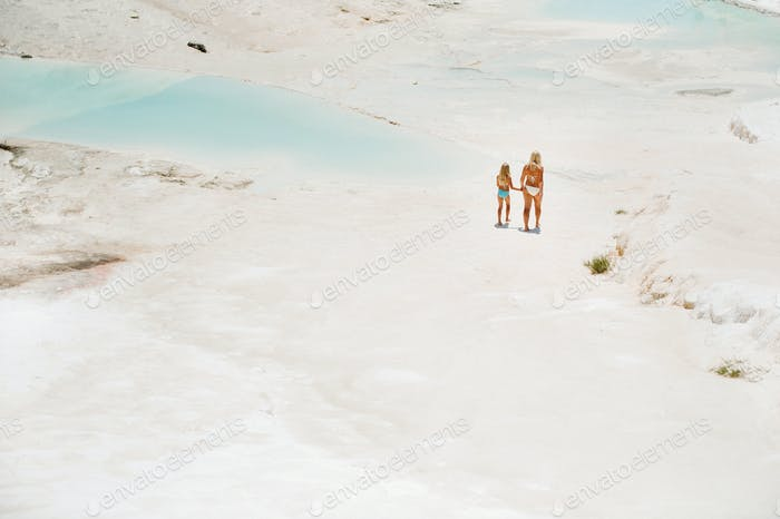 a little girl with her mother in bathing suits and sunglasses on a White mountain, a Family on a