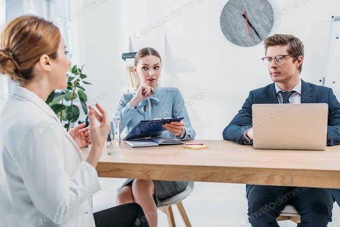 reclutadores mirando a empleados hablando en entrevista de trabajo
