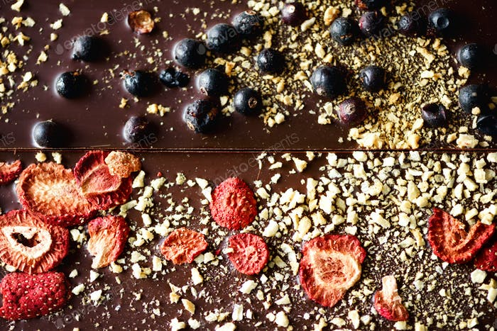 Handmade chocolate bars with dried cranberries, raspberries and pistachios, strawberries, nuts. Dark