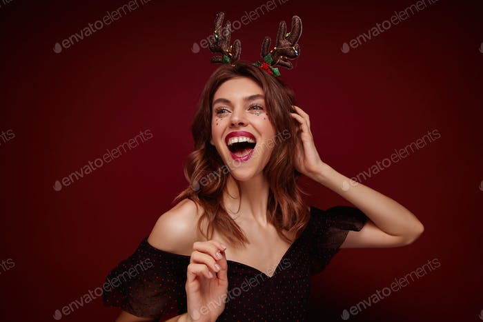 Indoor photo of beautiful joyful young brunette lady with festive hairdo wearing christmas horns