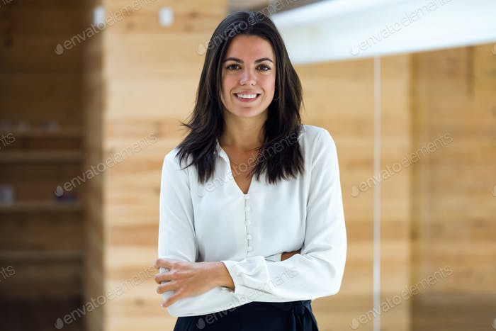 Smart attractive businesswoman looking at camera on coworking pl