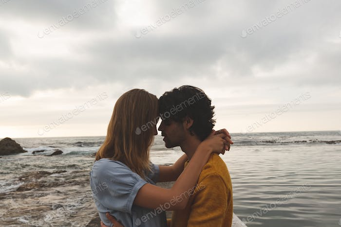 Side view of young Caucasian couple kissing each other standing on rock near beach