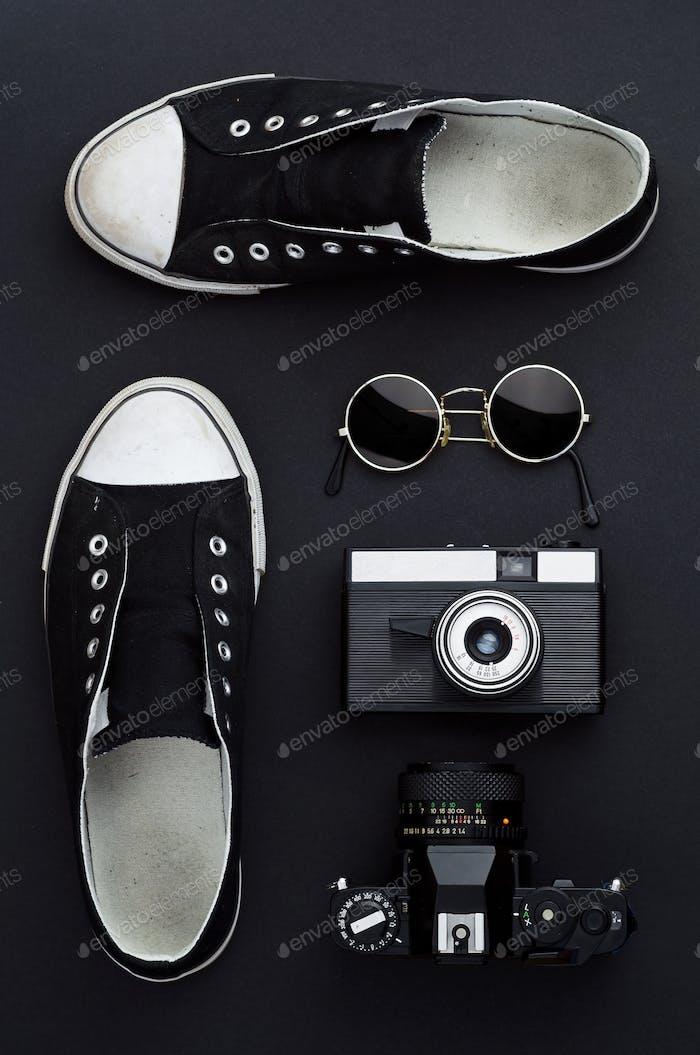 Sneakers, Fotokamera und runde Sonnenbrille