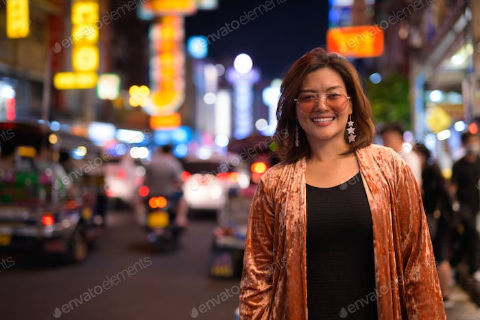 Young happy Asian tourist woman smiling and laughing at Chinatown
