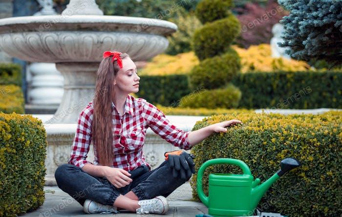 Proud gardener woman touching hedge in her well kept garden