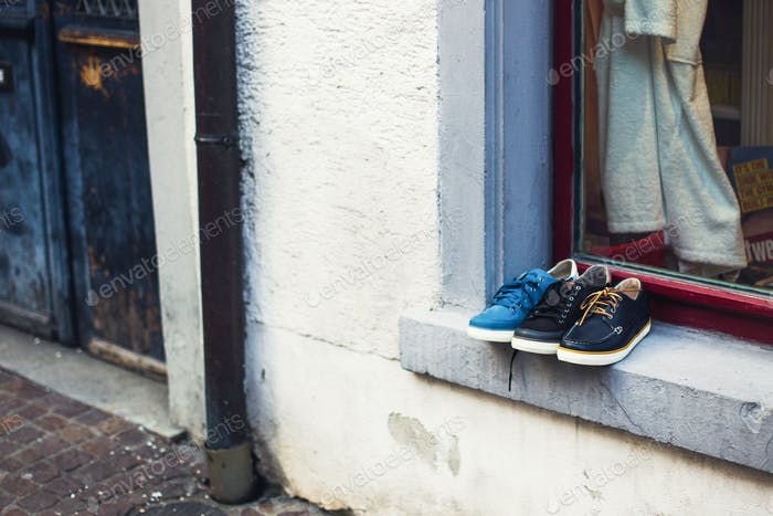 Showcases a shoe store, shoes on the windowsill outside
