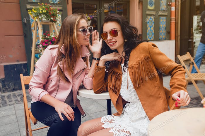 two young stylish women sitting at cafe, talking, gossiping, stylish trendy outfit