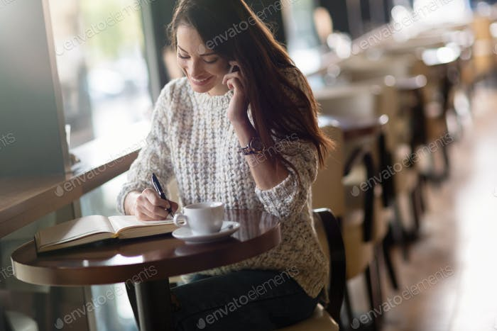 Beautiful woman working and studying in cafe