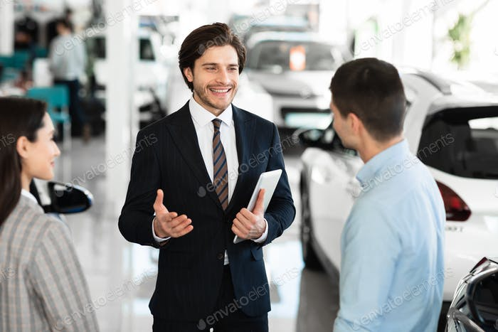 Car dealer talking with clients selling them automobile