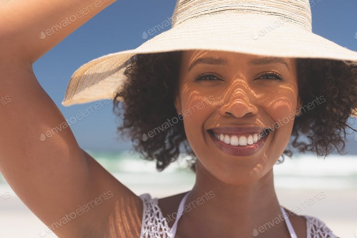 Beautiful young woman smiling and looking at camera standing at beach